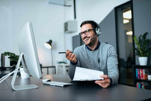 Handsome smiling man working at help desk.